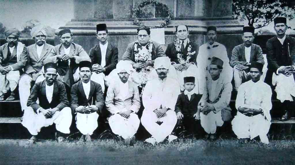 Bhimrao Ambedkar and his followers at the Vijay Stambhain  Bhima Koregaon, January 1, 1927. Tal. With Ambedkar at the centre, Shivram Janba Kamble who organised the meeting is to his left, wearing a garland. Others in the picture, in the Ambedkar row (left to right): SF Barathe, BJ Bhosle, SB Bhandare, JS Ranapise, PG Solanki, Shivram Janba Kamble, KM Sonawane and Ramchandra Krishnan Kadam. Second row (left to right): P Waghnare, BB Jadhav, Jivappa Lingappa Aidale, SR Thorat, KN Kadam, AS Kamble and KN Sonkamble. Credit: संदेश हिवाळे [CC BY-SA 4.0 (https://creativecommons.org/licenses/by-sa/4.0)], from Wikimedia Commons