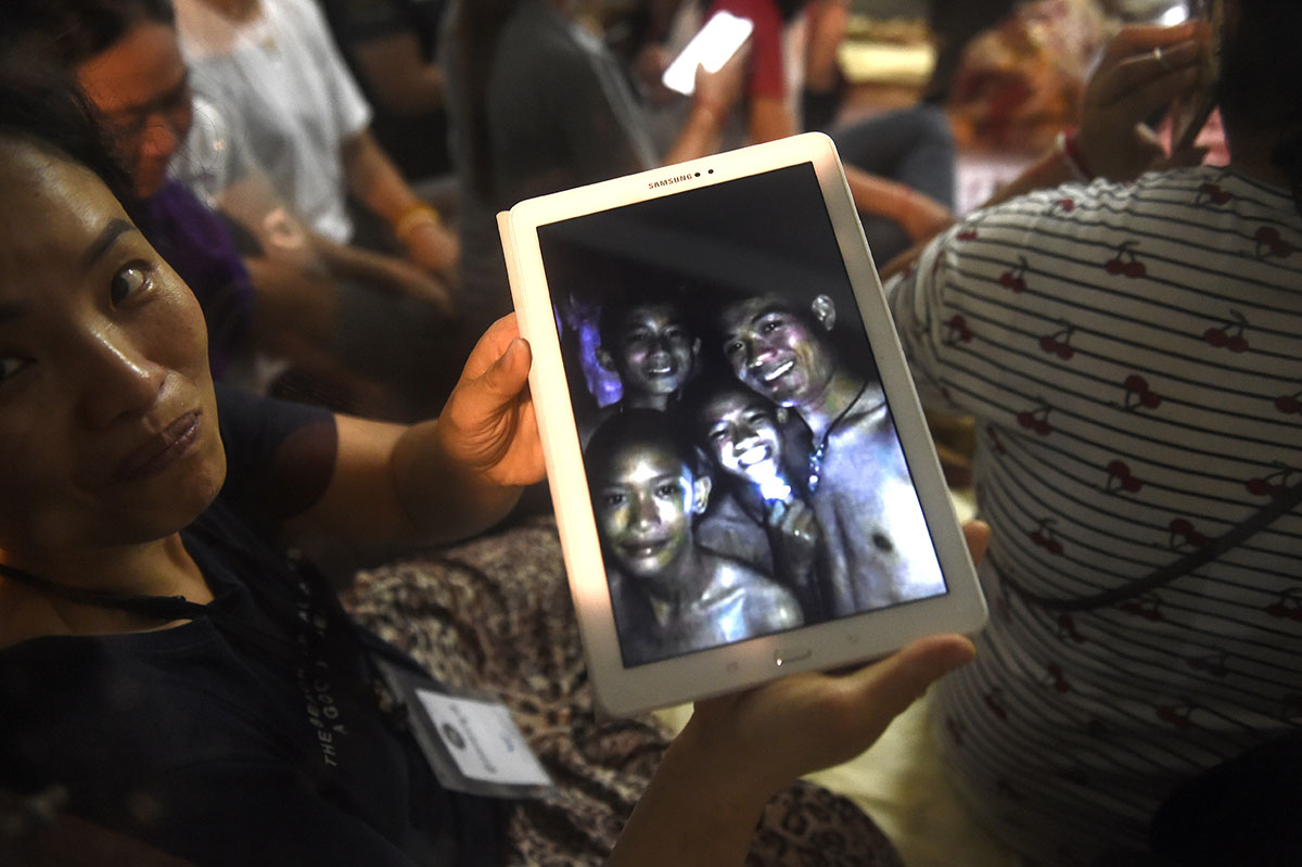 """Thanaporn Promthep, the mother of one of the 12 boys, displays an image believed to have been taken in 2017 of her son Duangpetch Promthep, nicknamed """"Dom"""" (pictured second from right) and his football coach Ekkapol Chantawong (right), after hearing the news the group was found, near the Tham Luang cave at the Khun Nam Nang Non Forest Park in the Mae Sai district on July 2, 2018. Twelve boys and their football coach trapped in a flooded Thai cave for nine days were found safe on late July 2.  Lillian Suwanrumpha/AFP"""