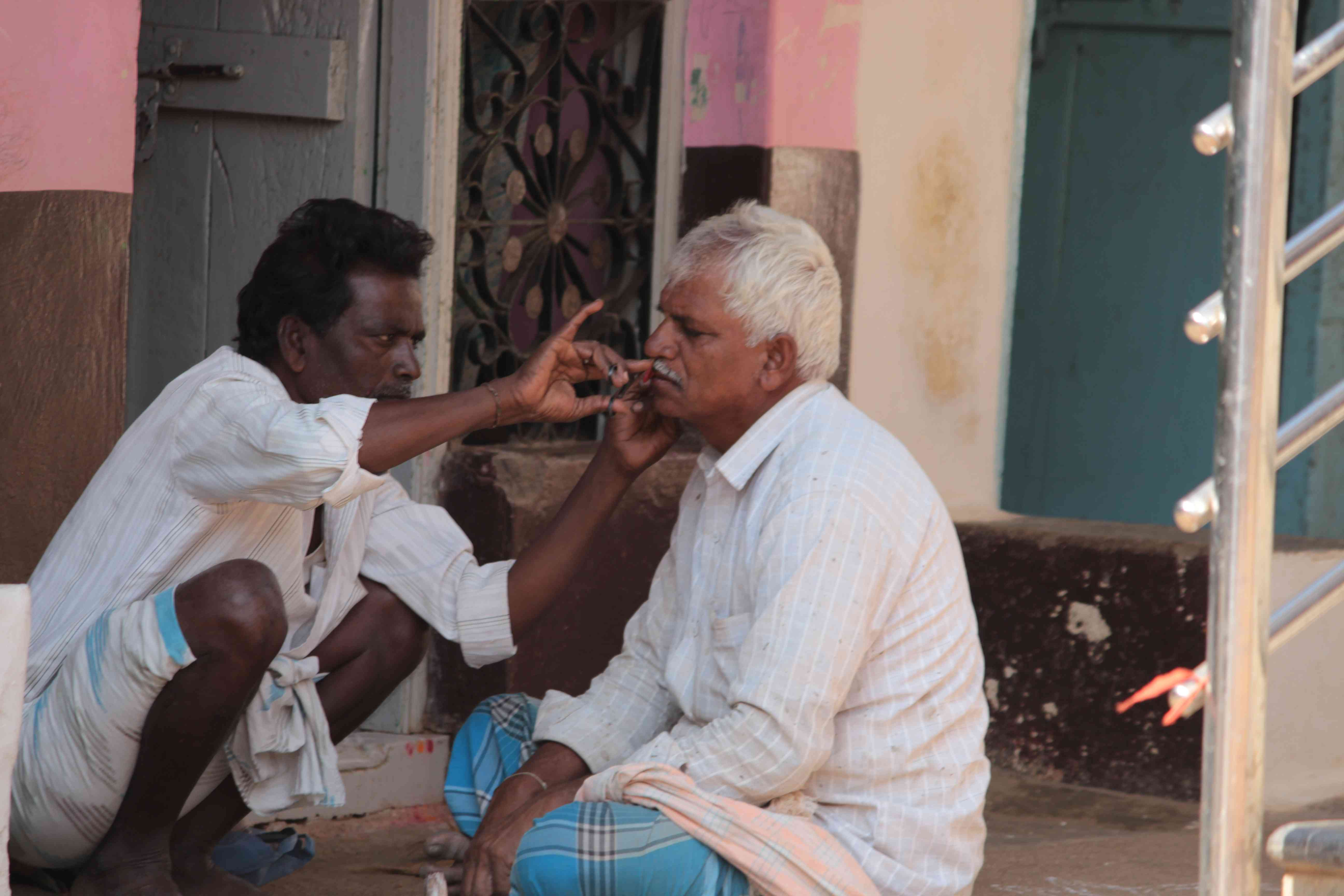 A barber at his client's home in Haranagiri village.