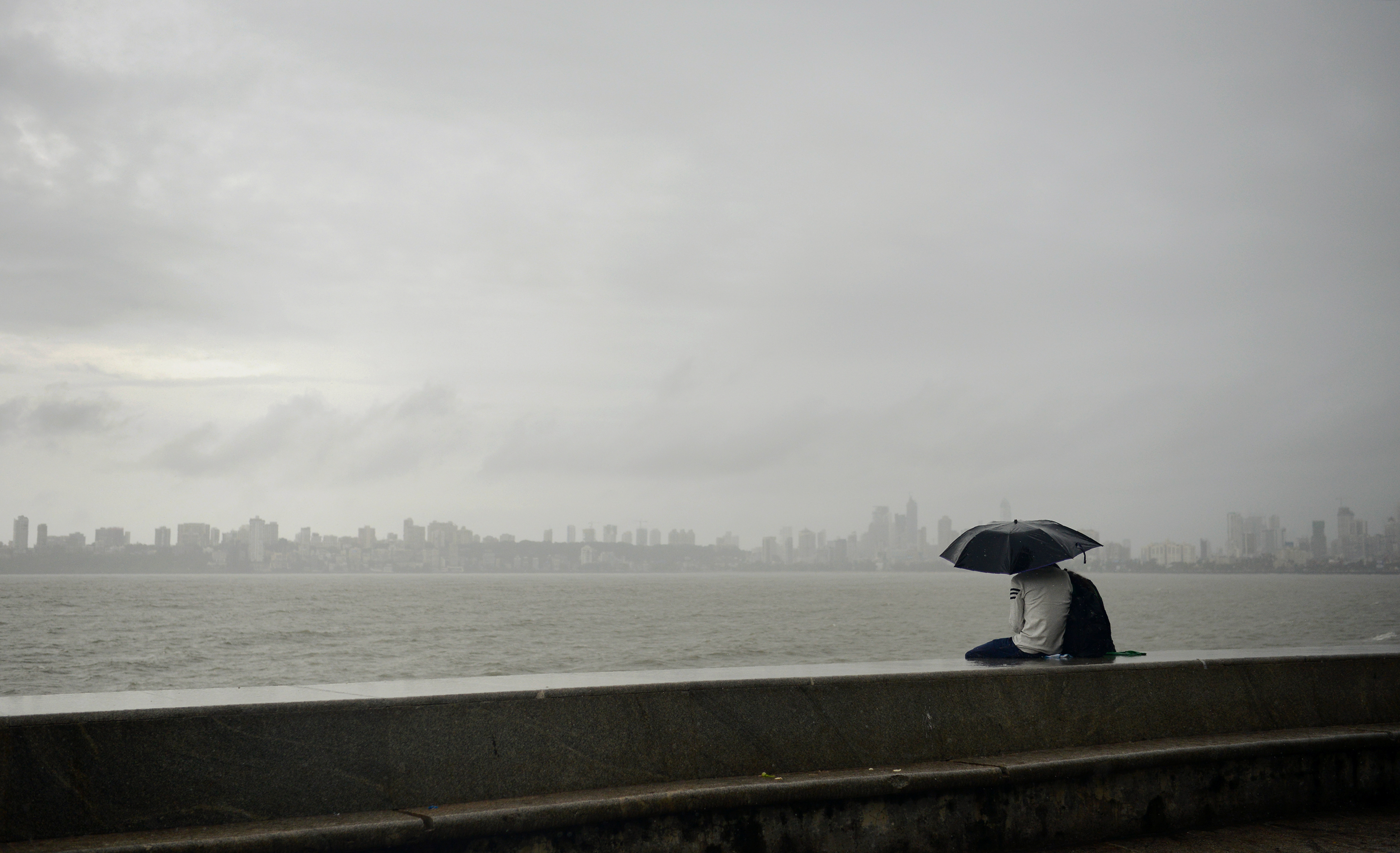 A couple watches the Mumbai skyline at Marine Drive. (Credit: Punit Paranjpe/AFP)
