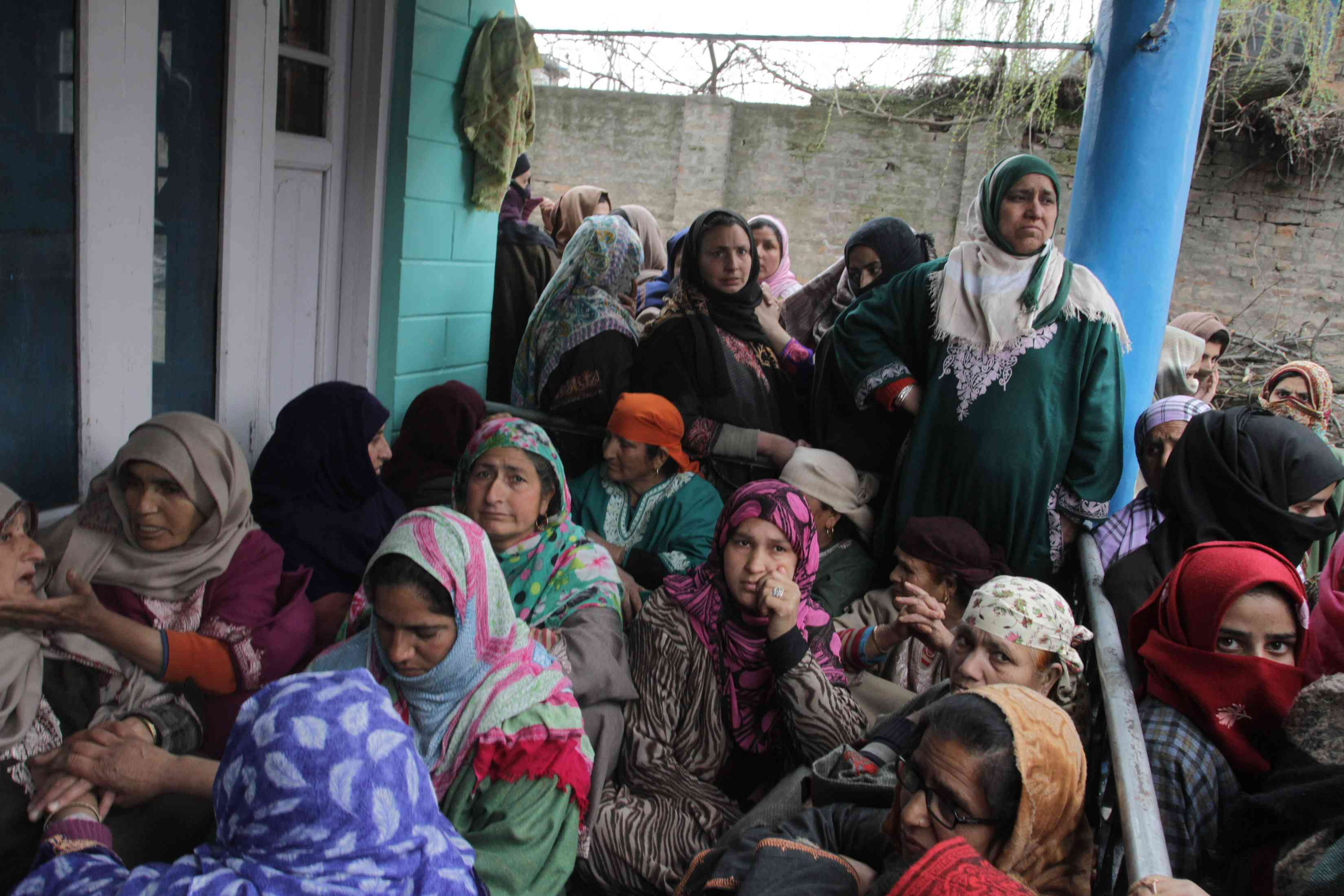 Mourners sit inside the compound of the Pandit family home in Awantipora on Tuesday. (Photo credit: Safwat Zargar).