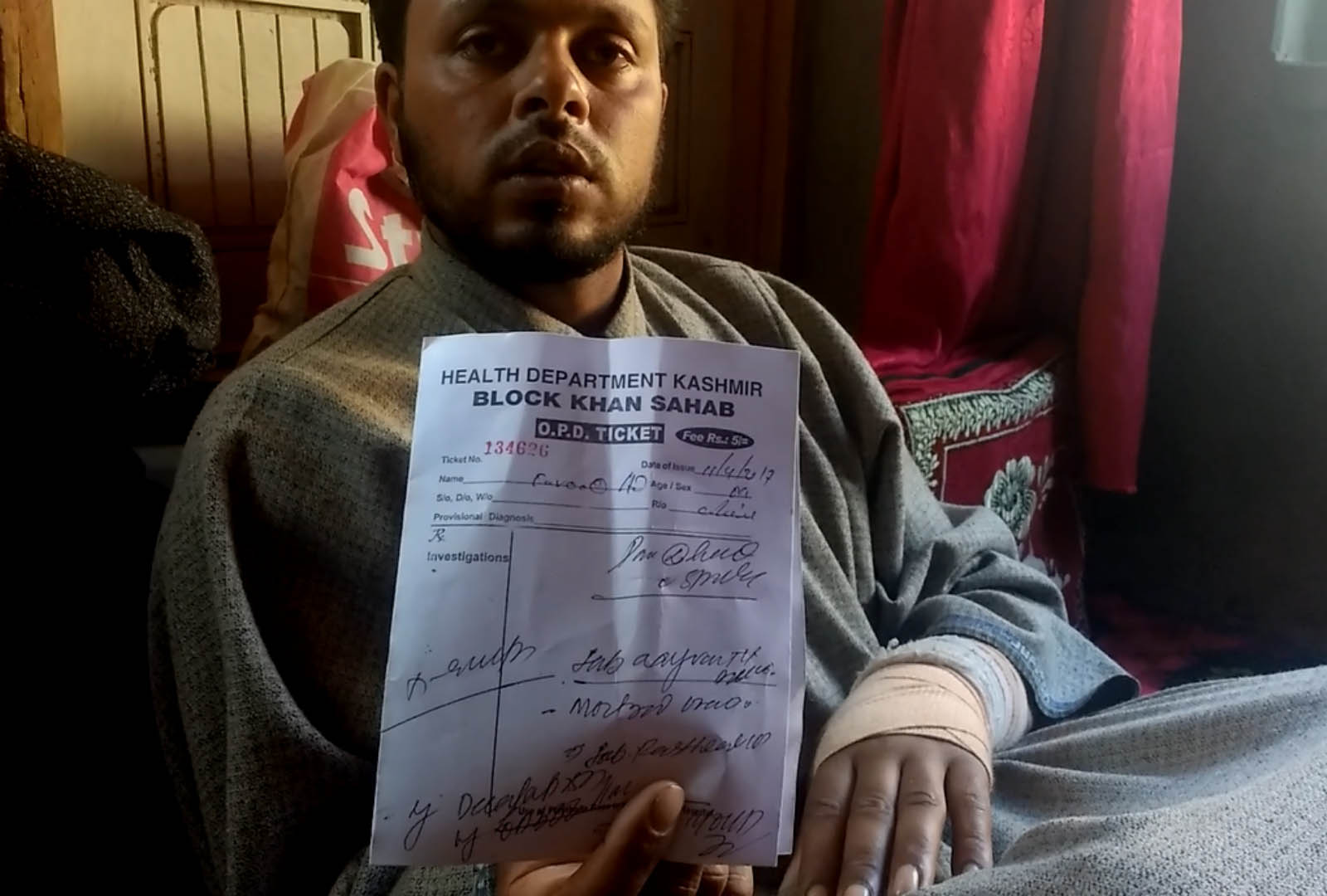 Farooq Dar displays his medical report. Credit: Rayan Naqash