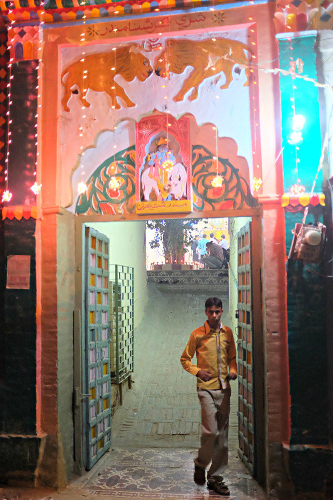 A kid passes through the main gate of the Krishna temple.
